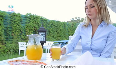 Blond woman pouring juice in a glass and drinks