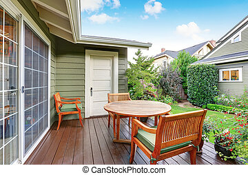 Back deck of guest house with wooden table set - View of...