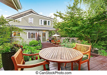 Back deck of guest house with wooden table set. Luxury house...