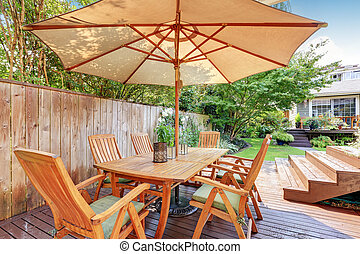 House exterior. Wooden patio table set with umbrella