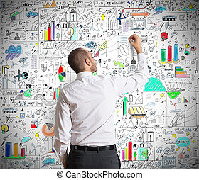 Business Concepts - Businessman draws on the wall of...