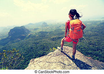 woman hiker looking from the mountain peak cliff