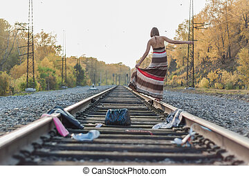 Beautiful girl walking on railroad track.
