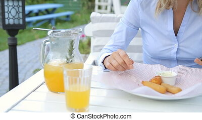 Woman hands texting on smartphone during breakfast in cafe.