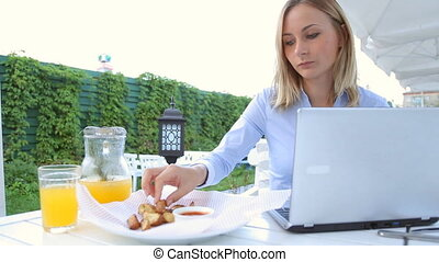 Young, happy woman eating salad in cafe in city