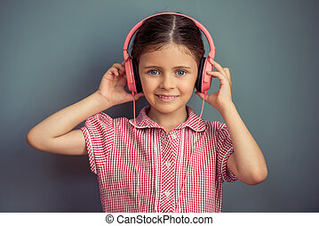 Charming little girl in cute dress and headphones is...