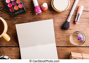 Empty greeting card laid on table. Make up products. - Empty...