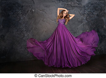 A woman in a violet dress - oung beauty woman in fluttering...