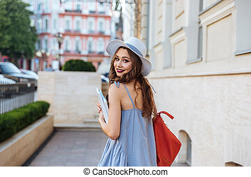 Happy woman with backpack and books walking in the city