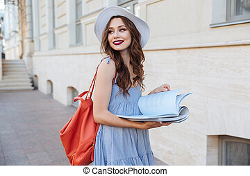 Happy pretty young woman reading a book on the street -...