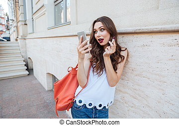 Young surprised woman holding lipstick and looking at her phone
