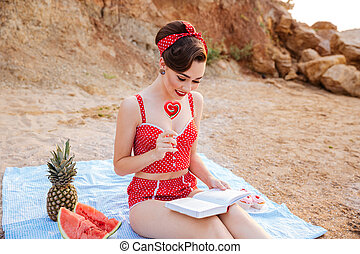 Pin up girl reading book and holding heart shaped candy -...