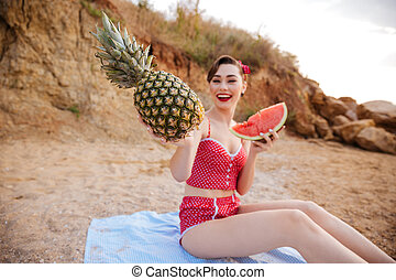Young pin up girl posing with fruits in her hands - Young...