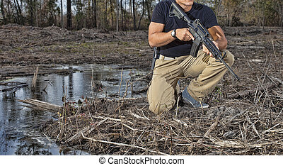 AR-15 - Man kneeling next to some water with an AR-15 and...