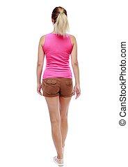back view of walking  woman. beautiful blonde girl in motion.