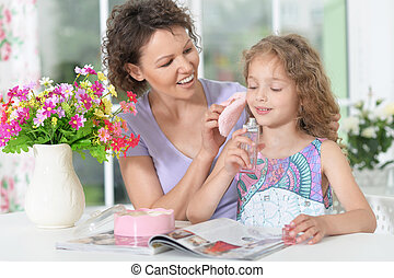 mother with little daughter with magazine - Smiling mother...
