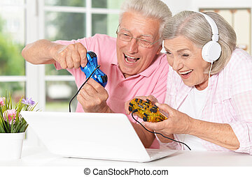 Senior couple portrait playing on laptop