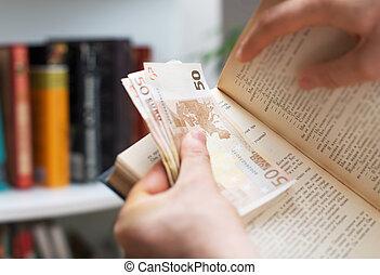 Man hiding money in a book. Secret stash place.