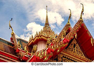 Thailand temple on a cloudy sky with the sun.
