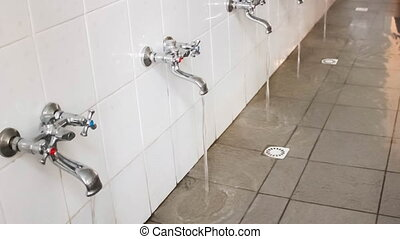 Rows of Steel Taps in the Bathroom - rows of steel taps in...