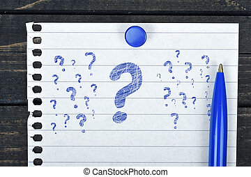 Question marks on page and pen on wooden table