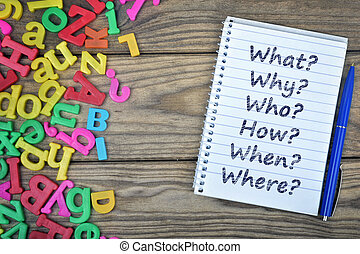 Questions text on notepad and magnetic letters on wooden...