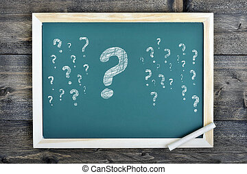 Question marks text on school board and chalk on wooden...