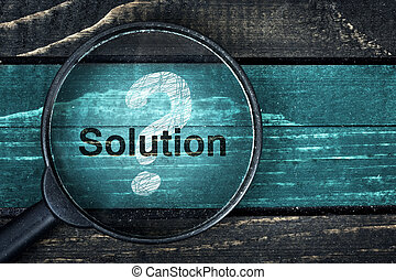 Solution text painted and magnifying glass on table -...