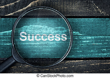 Success text painted and magnifying glass on table