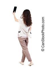 back view of standing young beautiful woman using a mobile...