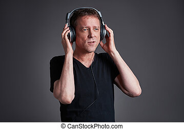 Man with a headphone - A middle age listening some music on...