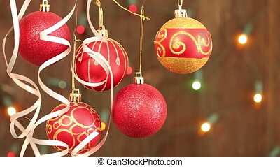 red Christmas balls hanging on strings. Flashing a garland...