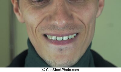 Adult man with bristle sing song in front camera. Open mouth. White teeth. Laugh
