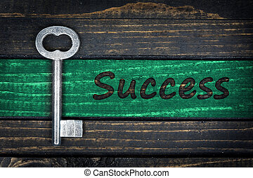 Success word and old key on wooden table