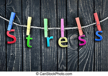 Stress word hanging on clips and wooden wall