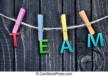 Team word hanging on clips and wooden wall