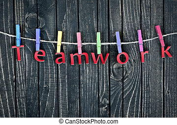 Teamwork word hanging on clips and wooden wall