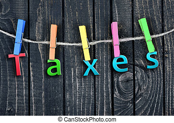 Taxes word hanging on clips and wooden wall