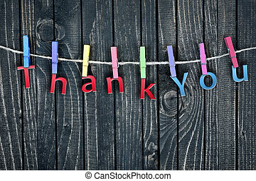 Thank You word hanging on clips and wooden wall