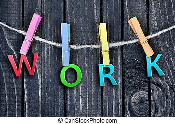 Work word hanging on clips and wooden wall
