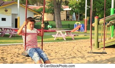 Cute little boy swinging at the playground - Elementary aged...