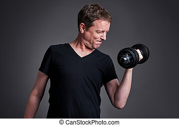 Middle age man with weights - A middle age man standing and...