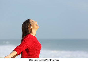 Woman in red breathing fresh air - Side view of a happy...