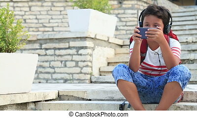 Schoolboy using smartphone - Young boy playing with mobile...