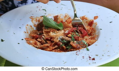 Eating pasta close up - Italian tomato sauce noodles on the...