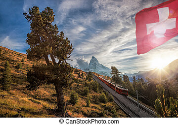 Matterhorn peak with a train and flag of Switzerland in...