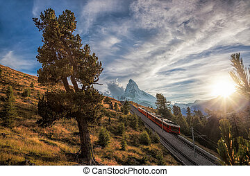 Matterhorn peak with a train against sunset in Swiss Alps,...