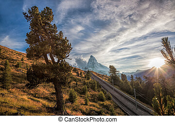 Matterhorn peak with railway against sunset in Swiss Alps,...