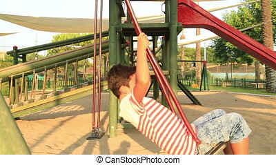 Happy child swinging at the playground - Elementary aged...