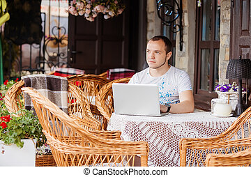 man in caffee works on his laptop